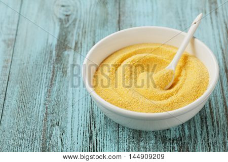 Corn meal or dry polenta in white bowl on vintage table.