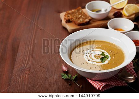 Lentil cream soup in a bowl with spices turmeric, paprika and garlic on wooden table. Copy space for text.