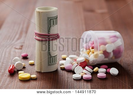 Heap of pharmaceutical drug and medicine pills scattered from bottles with dollar cash money. Cost of medicinal product and treatment concept.