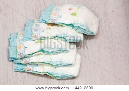 Accessory set for Baby disposable diapers on gray background tree items for baby care. Lay diaper nappy the parent taking care of a baby. safe baby ear sticks