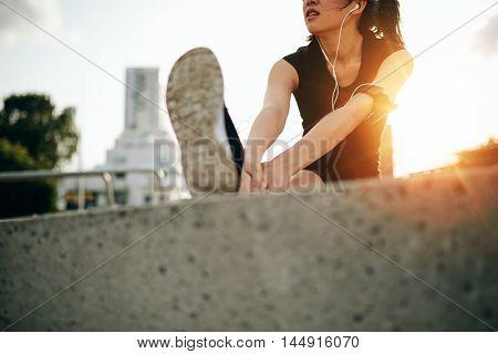 Female Runner Warming Up Before A Morning Run