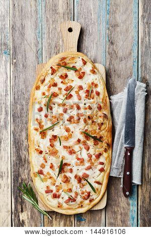 Tart Flambe or Flammkuchen on wooden cutting board decorated rosemary. Traditional Alsatian pie. Rustic style. Top view.