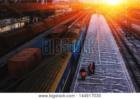 train and many cargo railcars at the platform at sunset