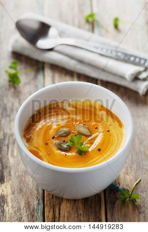 Fresh carrot and pumpkin soup in white bowl. Diet and detox concept. Organic vegan food.