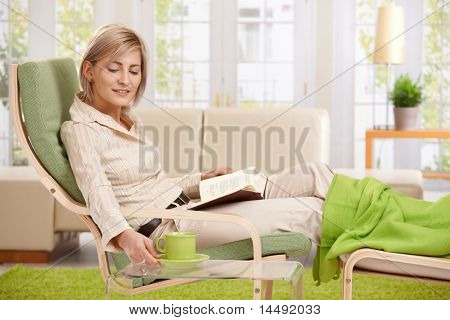 Woman relaxing in armchair at home, reading book with feet up, putting coffee on table, smiling.?