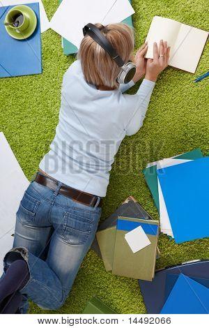 Junge Frau am Boden Lesebuch, Holding auf Headset mit Papieren rundum liegen.?