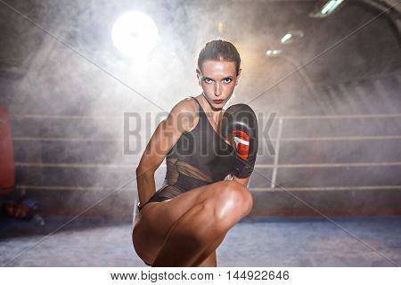Portrait of attractive blonde girl in black body and boxing gloves practicing kicks.Backlit