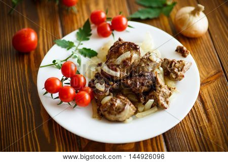 Fried chicken liver with onions on a plate with tomatoes