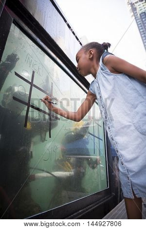 NEW YORK MAY 27 2016: An unidentified girl plays tic tac toe against a US Navy EOD technician on the glass of a 6,800 gallon mobile dive tank on Military Island in Times Square during Fleet Week 2016.