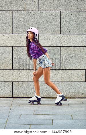 Beautiful young girl skating on roller skates on the background of gray wall in a park. Full length of happy young woman roller skating.