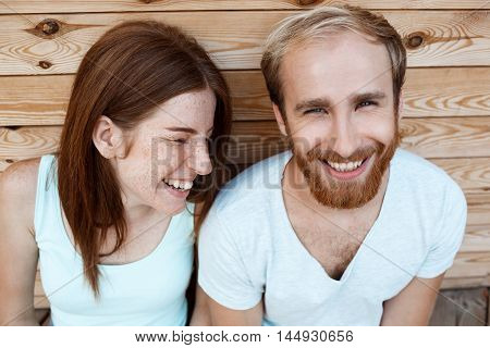 Young beautiful couple smiling, posing, wooden boards background