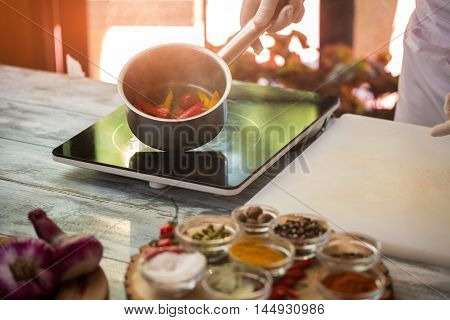 Hand in glove holds saucepan. Pieces of red vegetable. Boiled tomatoes for sauce. Only natural products.