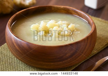 Cream of cauliflower soup in wooden bowl photographed on wood with natural light (Selective Focus Focus on the front of the cauliflower on the soup)