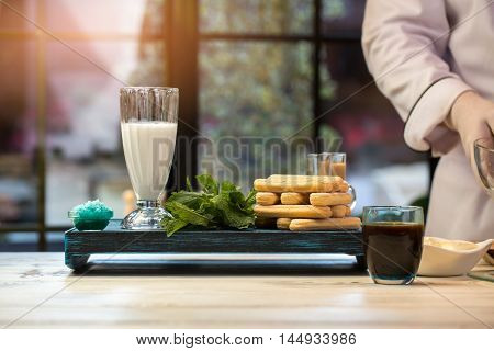 Green herb and biscuits. Glass with black drink. Coffee and savoiardi for tiramisu. All ingredients are fresh.