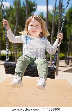 Little Kid Swinging At Urban Park