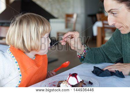 Woman Feeding Little Kid With Spoon Chocolate Cake