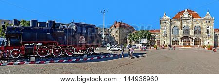 ARAD ROMANIA - AUGUST 26 2016: Panorama with old train station in Arad Romania and a steam locomotive ahead.