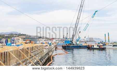 Hiroshima, Japan - March 16, 2016: A crane is working on a construction site near Miyajima Ferry.