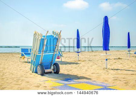end of summer beach deckchair closed umbrella