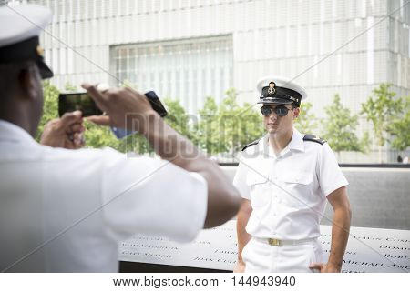 NEW YORK MAY 27 2016: A Canadian sailor serving on the Moncton 708 has his picture taken at the reflecting pools at One World Trade on the National September 11 Memorial site during Fleet Week 2016.