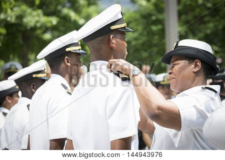 NEW YORK MAY 27 2016: US Navy sailor receives his promotion insignia during the re-enlistment and promotion ceremony held at the National September 11 Memorial site during Fleet Week 2016.