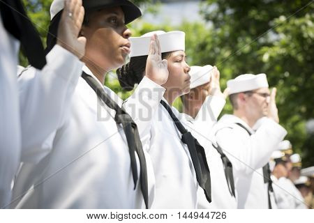 NEW YORK MAY 27 2016: US Navy personnel raise their hands to be sworn in during the re-enlistment and promotion ceremony at the National September 11 Memorial site.