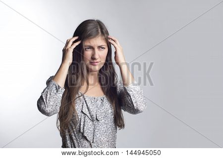 a young beautiful girl with long hair and headache