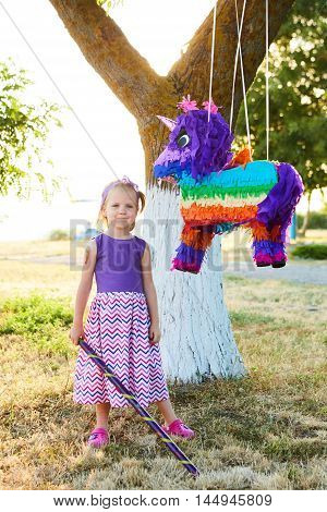 Young girl at an outdoor party hitting a unicorn pinata. Celebrating a birthday