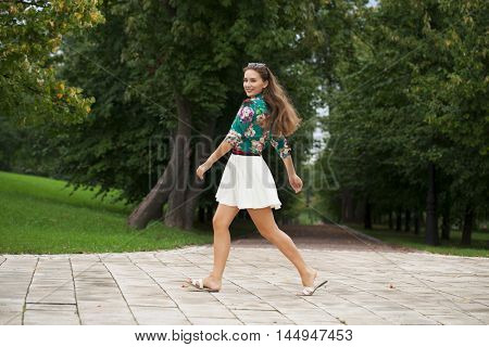 Young happy brunette woman in white skirt and blouse walking in the summer park