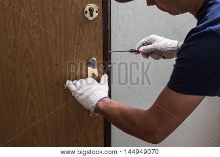 Man fixing the door with screwdriver, close up photo