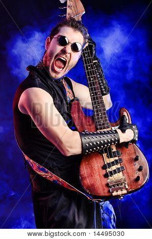 Heavy metal musician  is playing electrical guitar. Shot in a studio.