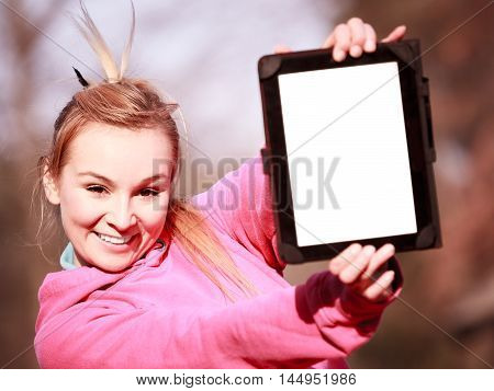 Fitness woman sport teenage girl in pink tracksuit showing blank copy space screen of tablet touchpad computer outdoor. Electronic technology.