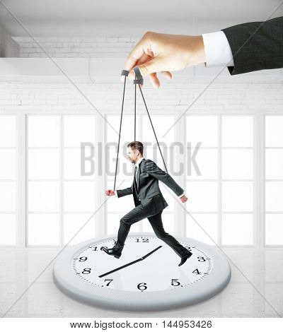 Huge hand making businessman run on abstract clock. White interior background. Manipulation and control concept