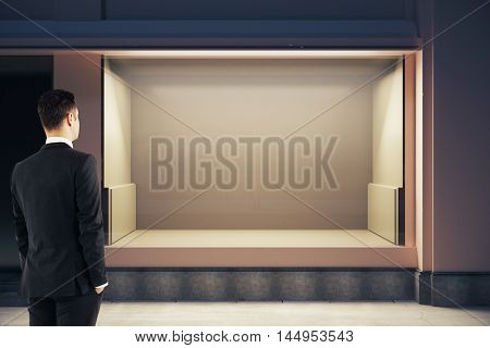 Young businessman looking at empty clean storefront at night. Mock up 3D Rendering