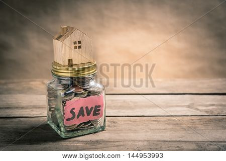 Wooden house on jar of coins with the word save. Saving concept. Vintage tone photo.