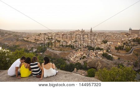 Toledo Spain - July 27 2016: Young people sitting on the stone enjoying peaceful magic moment of sunset over Toledo City Spain