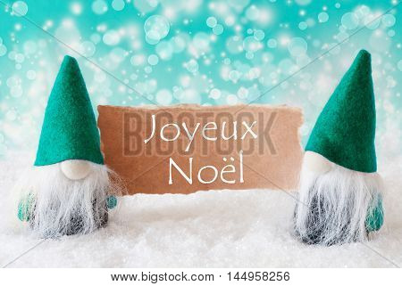 Christmas Greeting Card With Two Turqoise Gnomes. Sparkling Bokeh Background With Snow. French Text Joyeux Noel Means Merry Christmas