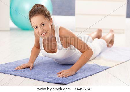 Hübsche junge Mädchen Übungen zu Hause, Erdgeschoss Lächeln.?