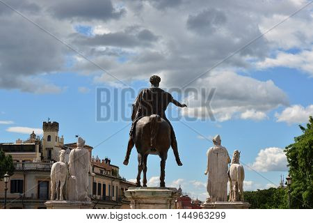 Ancient roman statue of emperor Marcus Aurelius with two Dioskouri against cloudy sky on Capitoline Hill in Rome