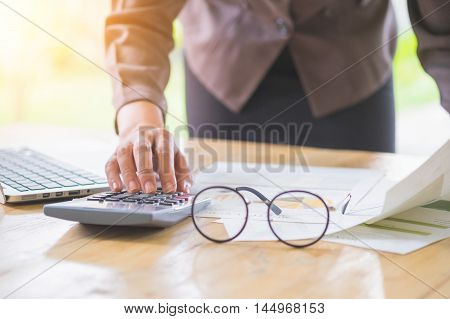 businesswoman working on Desk office business financial accounting calculate Graph analysis. vintage filter.