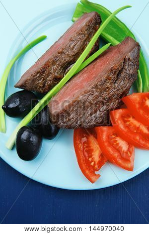 meat savory : grilled beef fillet mignon on blue plate with pepper chives and black greek olives over blue wooden table
