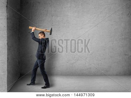 Side view of a businessman crashing concrete wall with hammer. Hard work. Reaching the goal. Achievement and success. Struggling. Copyspace.