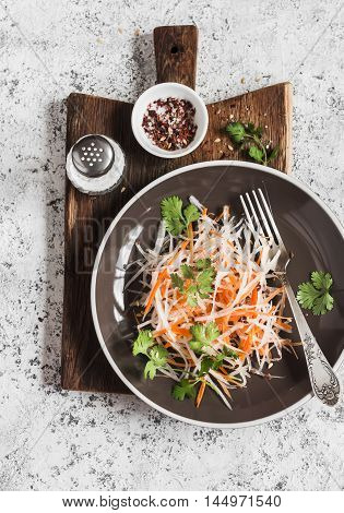 Daikon and carrot slaw. Healthy vegetarian food. On a light background top view