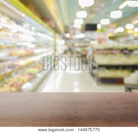 wooden table top with blur interior of supermarket with miscellaneous product on shelves