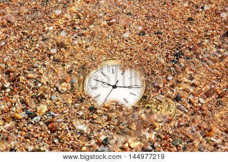 gold watch and sand of the sea on the coast