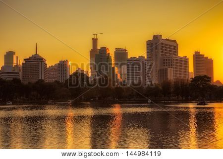 Sunset skyline from Lumpini park at Bangkok Thailand Edit warm tone