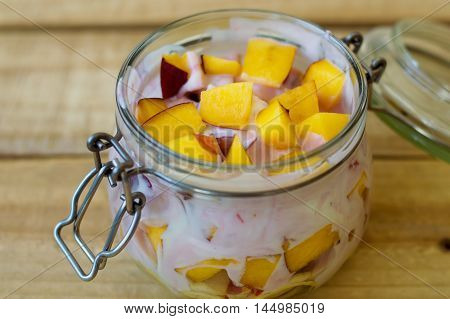 Fruit mix and fresh homemade yogurt in a glass food container for food storage. Healthy eating concept