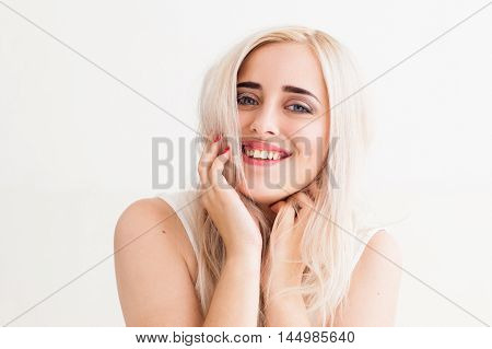 Sincere laugh of the beautiful blonde. Young woman widely smiling at camera with her hands on neck, white background