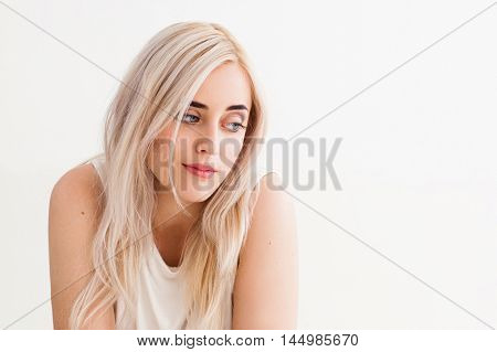 Portrait of young woman with contempt emotions. Beautiful disappointed blonde looking scornfully, white background