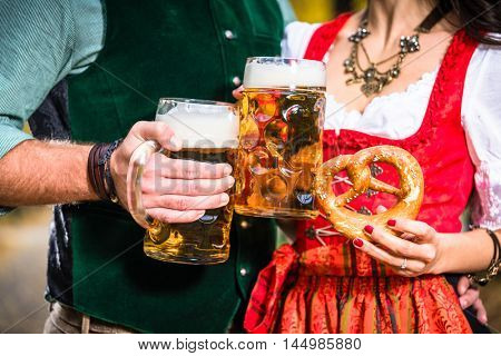 Hands holding Beer and Pretzels, detail of bavarian Tracht